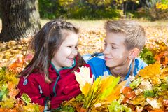 Queda Irmão e irmã com as folhas no outono Fotografia de Stock