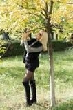 Queda, a mulher custa em uma árvore com folhas amarelas Imagens de Stock