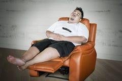 Queda obeso do homem adormecida durante a tevê dos relógios imagem de stock royalty free