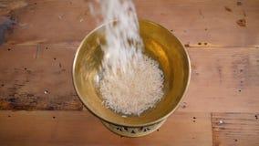 Queda seca do arroz basmati na bacia de madeira do metal do ouro na tabela do fim do movimento lento da mulher das mãos acima do  filme