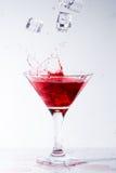 Quedas de gelo em um vidro com cocktail vermelho Imagens de Stock Royalty Free