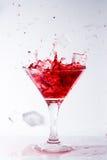 Quedas de gelo em um vidro com cocktail vermelho Imagem de Stock Royalty Free