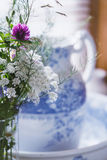 Queen Anne`s lace with clover in vase with blue and white water pitcher behind. Wildflower bouquet set in front of a water pitcher and a window behind Royalty Free Stock Images