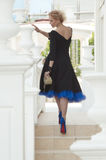 Queen in a black dress. Lovely Queen climbs the stairs Royalty Free Stock Image