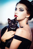 Queen and cat. Beautiful young woman with a crown on her head, holding a black cat on her arms Stock Images