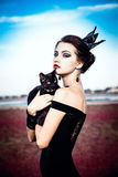 Queen and cat. Beautiful young woman with a crown on her head, holding a black cat on her arms Royalty Free Stock Photos