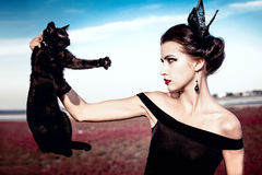 Queen and cat. Beautiful young woman with a crown on her head, holding a black cat at withers Royalty Free Stock Photo