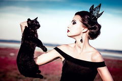 Queen and cat. Beautiful young woman with a crown on her head, holding a black cat at withers Royalty Free Stock Images