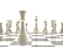 The queen chess piece in-focus. The queen chess piece standing infront of the rest of the pieces Royalty Free Stock Photos