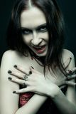 Queen of the damned. Pretty gothic girl posing over dark background royalty free stock image