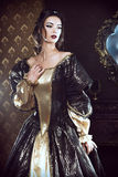 Queen dress. Renaissance Style -  beautiful young woman in the lush expensive dress in an old palace interior. Vintage style. Fashion Stock Images
