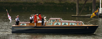 Queen and Duke of Edinburgh. Queen Elizabeth II and the Duke of Edinburgh, along with their footmen on the royal launch, at the start of the Thames Pageant to Royalty Free Stock Photography