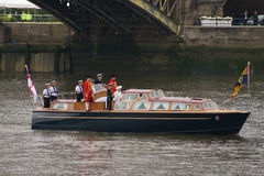 Queen and Duke of Edinburgh. Queen Elizabeth II and the Duke of Edinburgh, along with their footmen on the royal launch, at the start of the Thames Pageant to Stock Photos