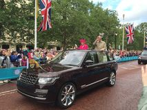 Queen and duke of Edinburgh. Queen Elizabeth second and husband Phillip driving in an open top Range Rover down the mall waiving at crowds. Duke Phillip Royalty Free Stock Photos