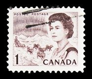 Queen Elizabeth II, northern lights and dog sled team, Centennial Definitives 1967-71 serie, circa 1968. MOSCOW, RUSSIA - FEBRUARY 10, 2019: A stamp printed in royalty free stock photos