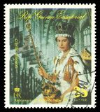 Queen Elizabeth II with symbols of royalty. Guinea Equatorial - stamp 1977: Color edition on 25th Coronation Anniversary, shows Queen Elizabeth II with symbols Royalty Free Stock Photos