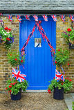 Queen Elizabeth photograph display on a blue door. Blue door with Union Jack bunting and Queen Elizabeth photograph display for the Diamond Jubilee celebrations Stock Photos
