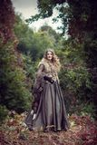 Queen in furs in the autumn forest. The medieval queen in furs in the autumn forest royalty free stock images