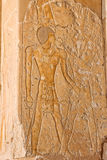 The queen Hatsheput . The queen Hatsheput being held by the god Amen- Ra on a side of one of the pillars at her temple in luxor Stock Image
