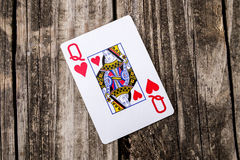 Queen of Hearts Card on Wood. Queen of Hearts from a deck of cards laying on vintage wood table background - old west salon style Royalty Free Stock Photography