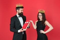 Queen of his heart. Man bearded king in tuxedo golden crown giving gift box to woman elegant dress. Royal family. Couple royalty free stock photography