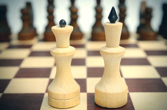 Queen and King on the background of other pieces on chessboard. Stock Photos