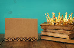 Queen/king crown on old book. vintage filtered. fantasy medieval period. Low key image of beautiful queen/king crown on old book. vintage filtered. fantasy stock photos