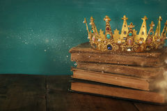 Queen/king crown on old book. vintage filtered. fantasy medieval period Royalty Free Stock Image