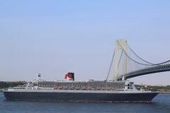 Queen Mary 2 cruise ship in New York Harbor under Verrazano Bridge heading for Canada New England. NEW YORK CITY - JULY 1: Queen Mary 2 cruise ship in New York Royalty Free Stock Photo