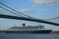 Queen Mary 2 cruise ship in New York Harbor under Verrazano Bridge heading for Transatlantic Crossing from New York to Southampton. NEW YORK CITY - AUGUST 15 Royalty Free Stock Photos