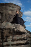 The queen of nature. Young blond in a long black dress stands in the middle of the rock Royalty Free Stock Images