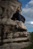 The queen of nature. Young blond in a long black dress stands in the middle of the rock Stock Photography