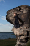 The queen of nature. Young blond in a long black dress stands in the middle of the rock against the background of blue sky, lake and grass Royalty Free Stock Photos
