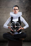 Queen of office, concept. Business lady in ruff collar with a clock looking at camera Royalty Free Stock Photography