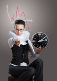 Queen of office, concept. Business lady in ruff collar with a clock pointing at the camera Stock Images