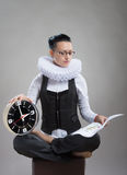 Queen of office, concept. Business lady in ruff collar with a clock reading a document Royalty Free Stock Photo