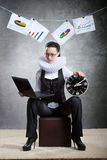 Queen of office, concept. Business lady in ruff collar with a clock using laptop Stock Image