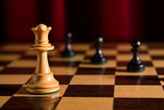 Queen and pawns against red Stock Photography