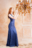 Queen, royal person with crown in blue dress. Chandelier Royalty Free Stock Image
