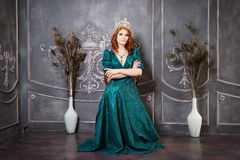 Queen, royal person with crown, red hair and green dress stock photos