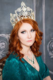 Queen, royal person with crown, red hair and green dress stock photo
