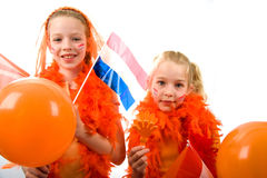 Queen's day. Young girls posing in orange with balloon and flag, isolated on white background stock images