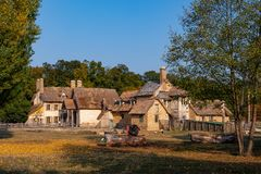 The farm of the hamlet of the queen in the park of the castle of. The queen`s hamlet farm with its thatched roofs serves as a refuge for retired old animals royalty free stock photo
