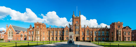 The Queen`s University of Belfast. With a grass lawn in sunset light. Wide panorama Stock Photos