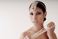 Queen of Sheeba. A well made up model cosseting her pearl necklace with her stunning olive compextion Stock Photography
