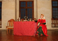 Queen Sitting by the Dining Table. Queen crossing her leg in red dress sitting by the dining table as a summer 2015 performance at Svihov Water Castle, Western Royalty Free Stock Photo