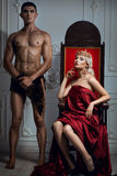 Queen sitting on a throne. Nearby is an athletic slave. Stock Photo