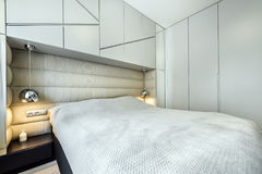 Queen size bed in grey room. Modern bedroom in gray finishing and queen size bed stock photography
