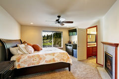 Queen size bed in luxury bedroom with fireplace. And bathroom . Northwest, USA stock photography