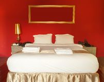 Queen size white bed in bedroom . Queen size white bed in red bedroom royalty free stock photo